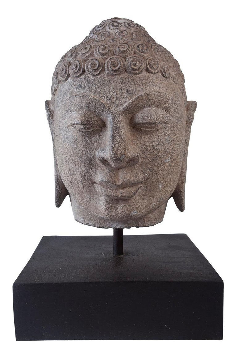 A lovely granite Buddha head on wooden base, early 1900s, India Features include the typical curled hair, elongated ears, half-closed eyes and serene smile. The Ushnisha crown depicts the wisdom and illumination after attaining enlightenment. Just