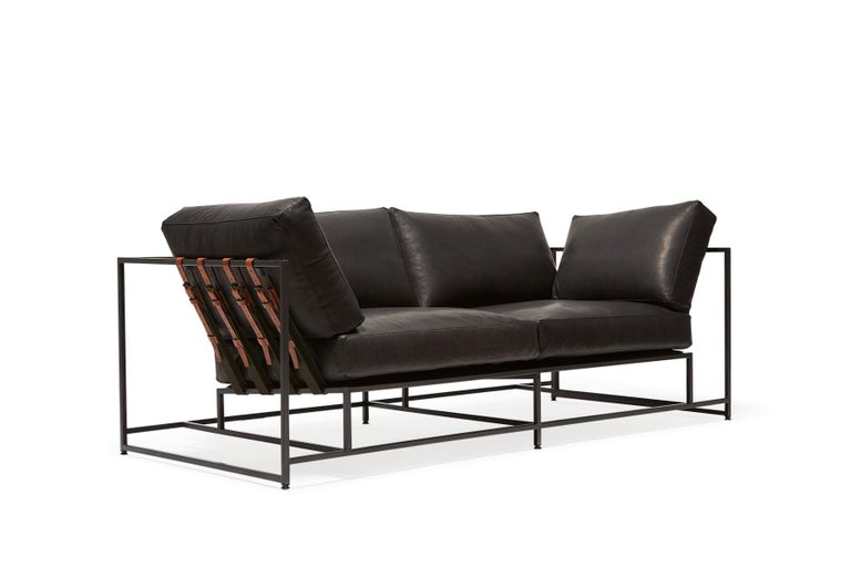 Slightly smaller in size, the two seat sofa is ideal for apartments or smaller spaces requiring a smaller footprint.  This variation is upholstered in a smooth, dark granite leather. The foam seat cushions have been wrapped in down, allowing for a
