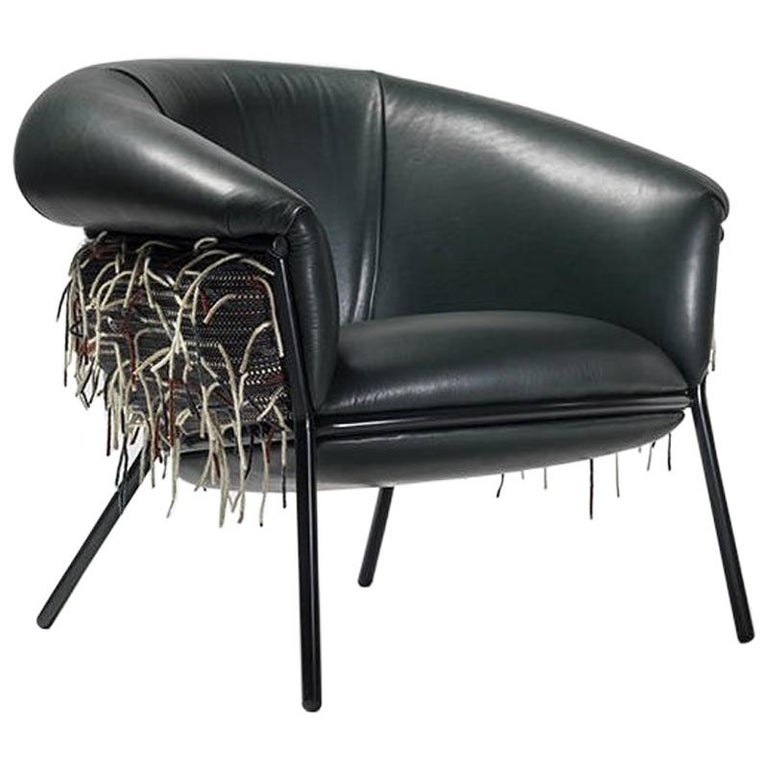 An iron tubular (25 mm) structured armchair. Seat and backrest upholstered in leather and fabric.