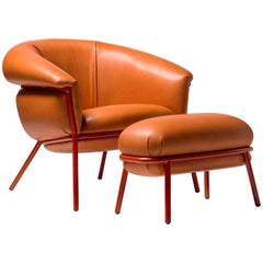 Ultra comfort armchair and footstool upholstered in leather and metal frame