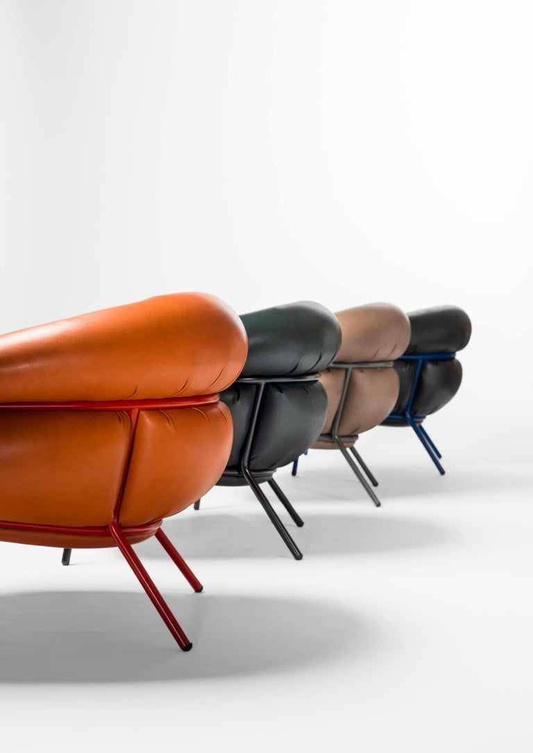 Tubular steel frame (25 mm) armchair. Seat and backrest upholstered in different leather finishes provided by BD. Optional tubular steel frame (25 mm) footstool upholstered in different materials provided by BD.