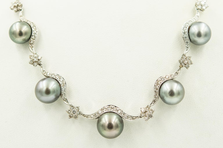 18k white gold necklace with diamond swags or scallops with diamond flower spacers and five graduating gray round cultured pearls draping across the front.  The necklace has a plunger clasp with a figure eight safety. The pearls measure