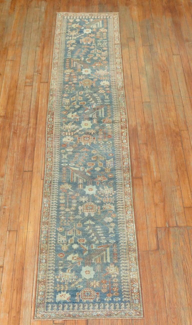 A long and narrow decorative earth toned Persian Malayer runner.
