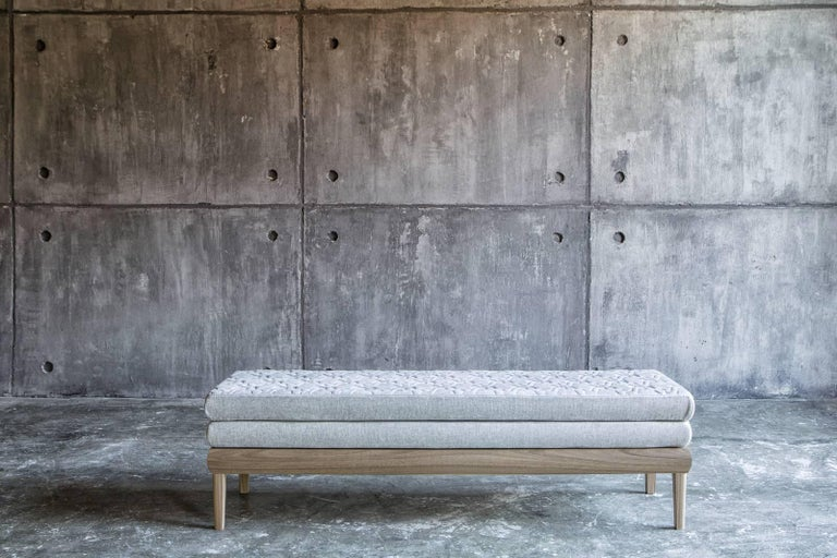 An elegant seating option that suits modern and traditional settings alike, this bench frame is made of Canaletto walnut with straight legs and a solid base that give it an architectural aesthetic. The rectangular cushions are upholstered in a