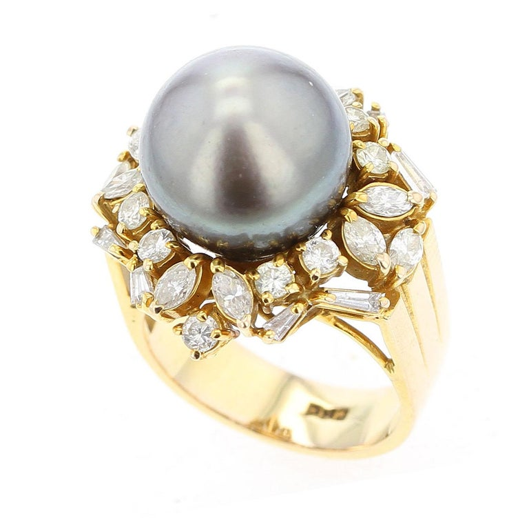 A bold ring consisting of Gray Tahitian Cultured Pearl (appx. 12.7MM) set with 10 round diamonds, 10 marquise diamonds, and 8 baguette diamonds. Ring Size US 5. Stamped 585. 14K Yellow Gold.