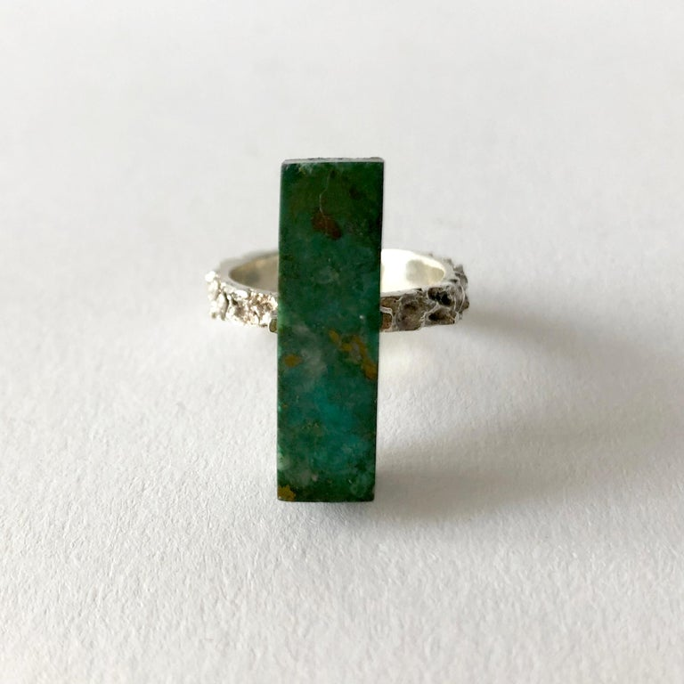 Heavily textured sterling silver ring with rectangular six sided malachite stone mounted on a sterling plank.  Ring is a finger size 7.5 and signed Peru, 925.  In very good vintage condition.