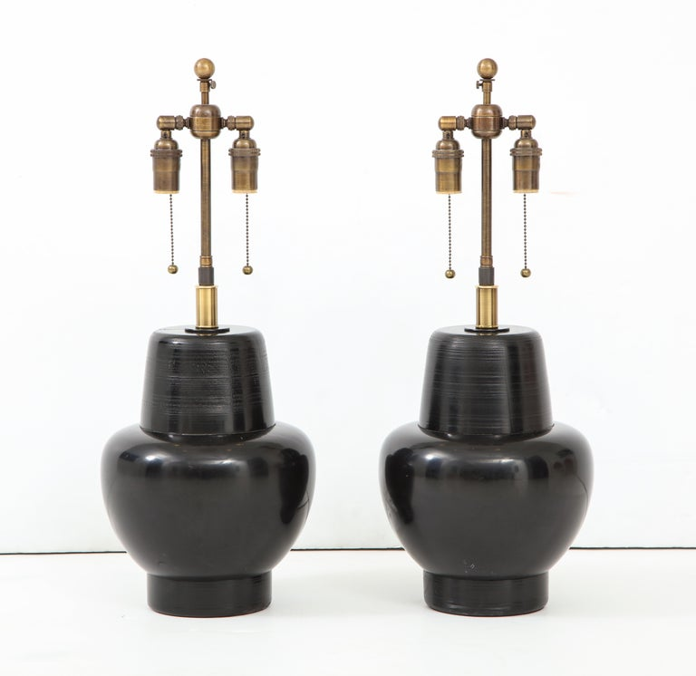 Wonderful pair of 1950s wooden lamps by James Mont. The lamps have a black lacquered finish and they have been newly rewired with antique brass double clusters. The height just to the top of the wooden lamp body is 13.5