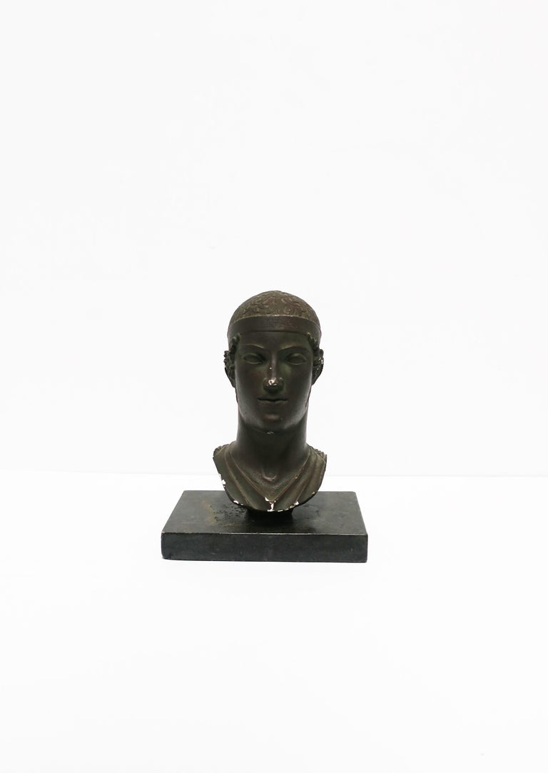 A mid-20th century Greco-Roman sculpture head or bust, England, 1965. A reproduction piece made of chalkware or plaster with a dark bronze-like finish. Marked on side as show in image #17. Vintage stone plinth base also included.