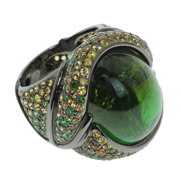 Green 23.30 Carat Tourmaline Yellow Sapphire Tsavorite 18 Karat Black Gold Ring Absolutely spactacular Green oval Cabochon shape Tourmaline weighing 23.30 Carat surrounded by 18K Black Gold and mix of Tsavorites and Yellow Sapphires inspires