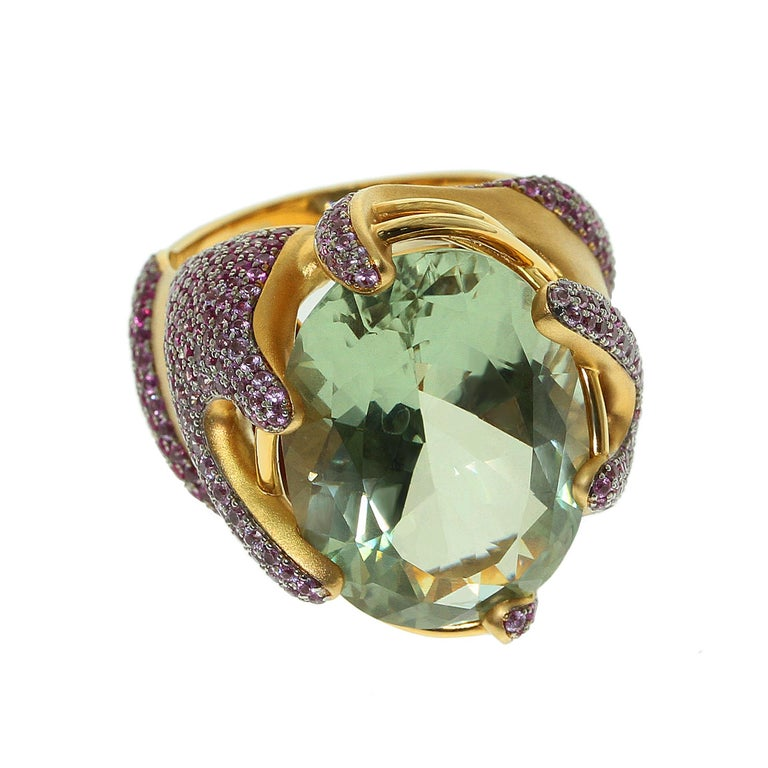 Green Amethyst Pink Sapphire 18 Karat Yellow Gold Ring Green Amethyst weighing 16.13 carat is the center of the designer's artistic project. Yellow 18 Karat Matte Gold perfectly set off the shimmer of Pink Sapphires. Gold remind us the shape of