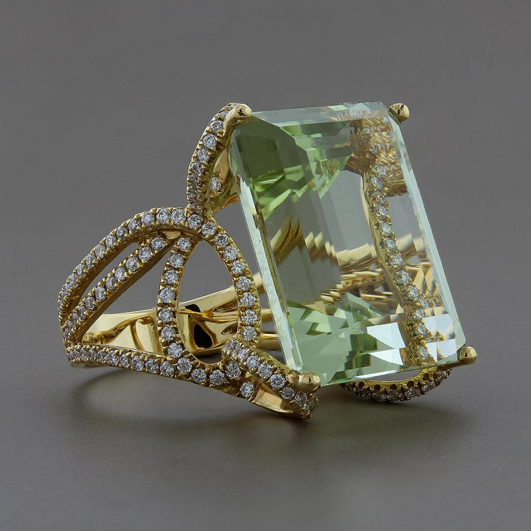 A modernly designed 25.48 carat, emerald cut, green aquamarine. In a whimsical setting of 1.38 carats of VS quality diamonds.  Set in 18K yellow gold.  Ring size 6 3/4