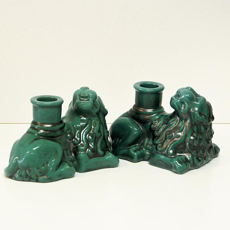 Pair of majestic green lion candlelight figurines in lying position. Holed underneath with stamp from Uppsala, St. Erik. Made of ceramic and glaced. This vintage lion candle light pair would look amazing displayed on a fireplace mantel or book shelf