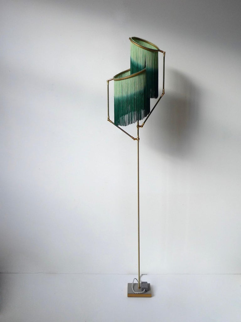 Green charme floor lamp, Sander Bottinga  Dimensions: H 153 x W 38 x D 25 cm Hand-Sculpted in brass, leather, wood and dip dyed colored Fringes in viscose. The movable arms makes it possible to move the circles with fringes in differed
