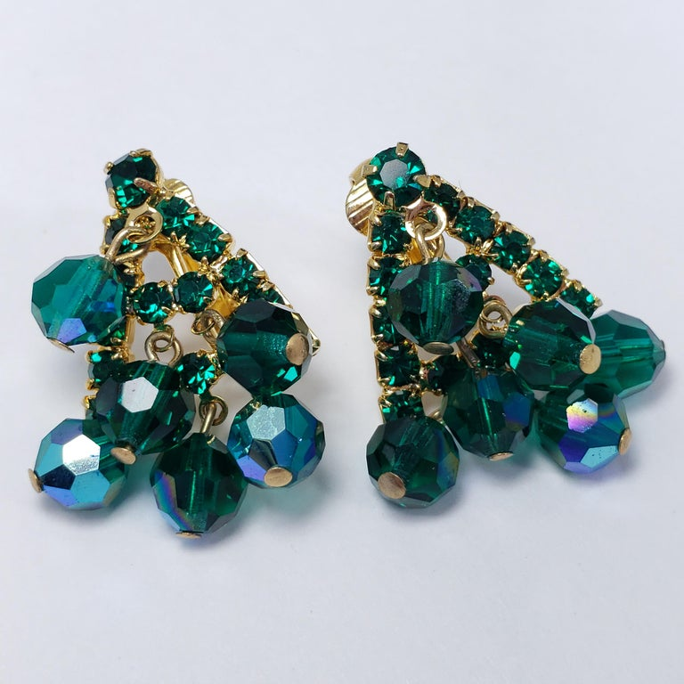 A pair of extravagant crystal cluster clip-on earrings by an unknown mid-1900s designer. Each earring features a triangular gold-tone metal setting, accented with prong-set crystals and dangling beads. Clip on backs. Stylish!
