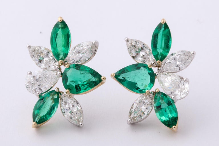 A unique pair of cluster earrings with a POP of color!  2.18 carats of white pear shape and marquise cut diamonds  2.01 carats of fine green pear and marquise cut emeralds   18k white and yellow gold   A 3/4 of an inch long and a little over half