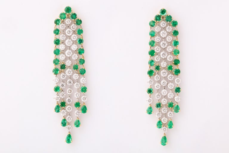 An beautiful earring with fantastic movement.  6.19 carats of white round brilliant cut diamonds   7.00 carats of fine vivid green round and pear shaped emeralds.   18k white and yellow gold.   Approximately 2.55 inches long and .60 inches wide.