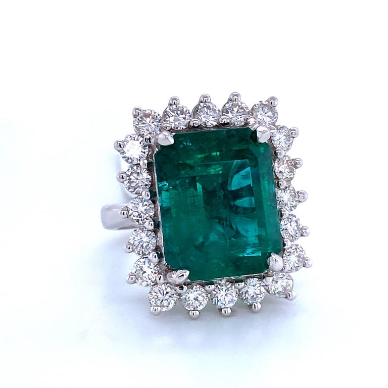 18K White gold cocktail ring featuring one green emerald cut Emerald weighing 12.35 carats flanked with 20 round brilliants weighing 2.10 carats,