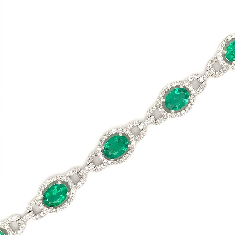 18K White gold bracelet featuring 9 green oval cut emeralds weighing 6.94 caras and 306 round brilliants weighing 2.10 carats. Color G-H Clarity SI