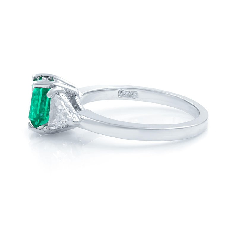 A bright vibrant crystalline green Colombian emerald, unusually fashioned as a soft shouldered square emerald-cut, radiates between sparkling white trillion-cut diamonds in this classic estate jewel rendered in lustrous platinum. Timeless. Material: