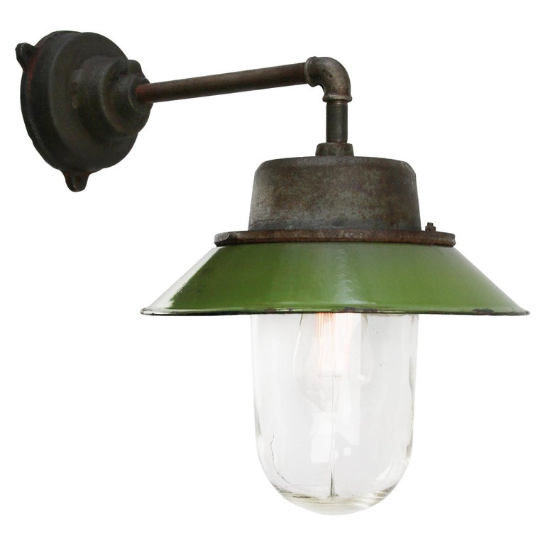 Green enamel Industrial wall light. Cast iron top. Clear glass.  Diameter cast iron wall piece: 12 cm. Three holes to secure.  Weight: 6.5 kg / 14.3 lb  Priced per individual item. All lamps have been made suitable by international standards