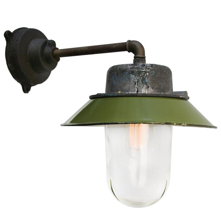 Green enamel industrial wall lamp with white interior. Grey cast aluminium top, cast iron arm Clear glass   Diameter cast iron wall piece: 12 cm. Three holes to secure.  Weight: 4.00 kg / 8.8 lb  Priced per individual item. All lamps have