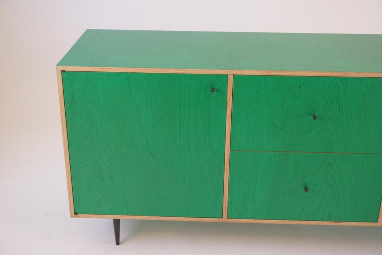 This version of the Classic Finn Ply cabinet, in the brand new shade of Green! This cabinet features a center section of drawers on wooden slides, and two sections with doors and adjustable shelves. The turned bronze knobs and legs have an oxidized