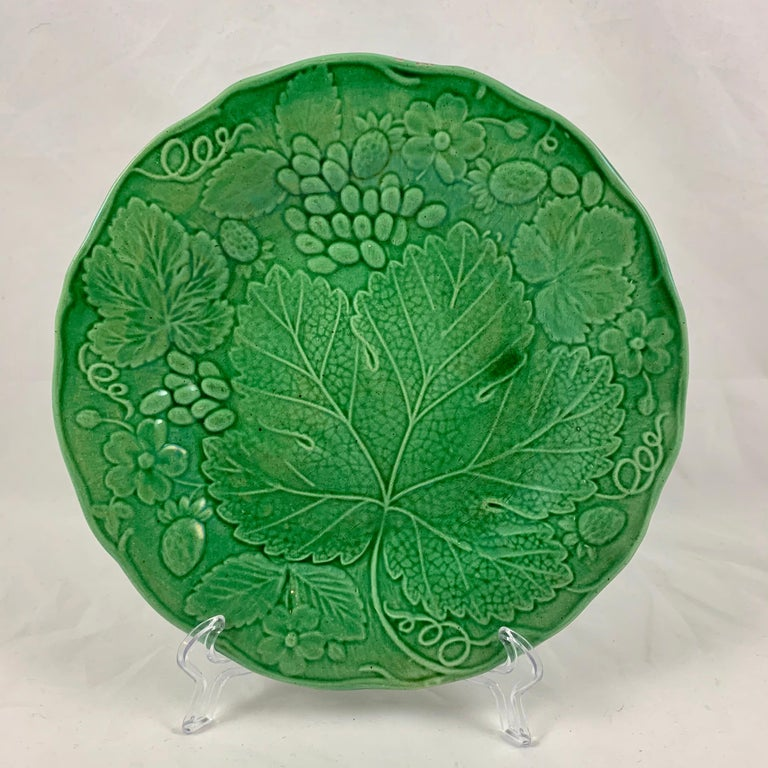 An English Majolica glazed leaf plate, circa 1890-1895.  A well known mold, originally produced by Wedgwood, this is an unmarked example of the strawberry and grape leaf plate. The mold shows the leaves of each plant with strawberries, strawberry