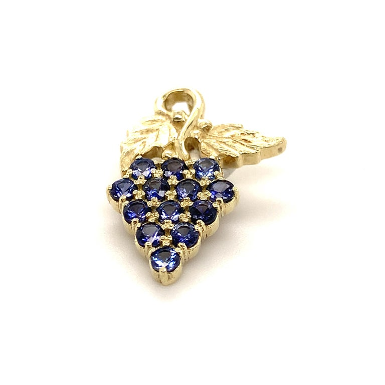 This smaller size grape pendant is done in 14-karat green gold to represent the leaves and the 13 Benitoites represent the grapes and weigh a total of 0.69 carats.   Benitoite is the California State Gemstone and is one of the 10 rarest stones in