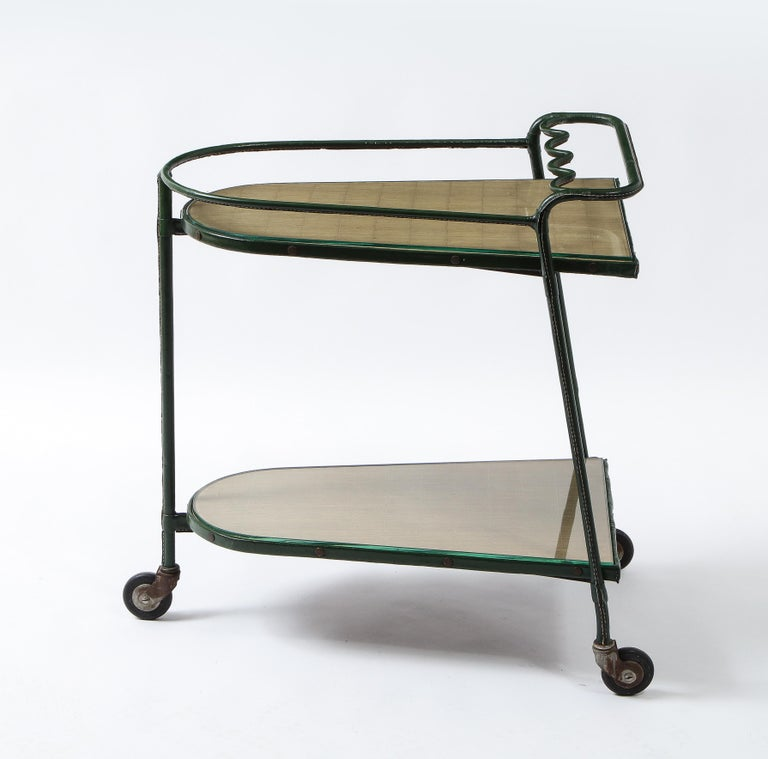 Exceptional bar cart by Jacques Adnet, an abundance of details on this piece, from the waffle paper-covered trays to the brass screws, acorn nuts, and unusual tri-legged construction. It retains its original glass tray covers.
