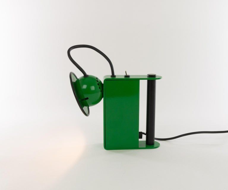 Green Minibox table lampdesigned byGae Aulenti & Piero Castiglioniand manufactured by Stilnovo in 1980.  This halogen table lamp can also be used as a 'torch' thanks to the handy handle. However, due to the power cord, it can only be used