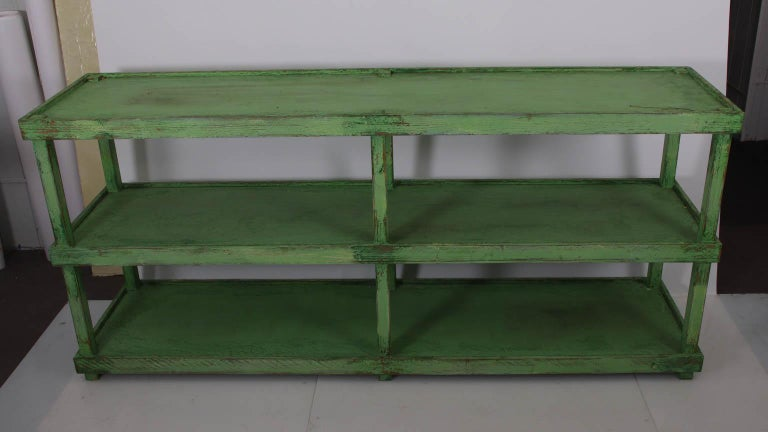 Green painted two-tier pottery table with three shelves. Please note of wear consistent with age including chips and paint loss throughout due to daily use.