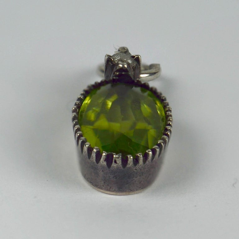 A silver charm pendant mounted with an oval-cut green peridot topped with a rose cut white diamond.   The peridot measures 9.5 x 5.9 x 3.12mm and has an approximate weight of 1.17 carats. The diamond measures 2mm in diameter and has an approximate