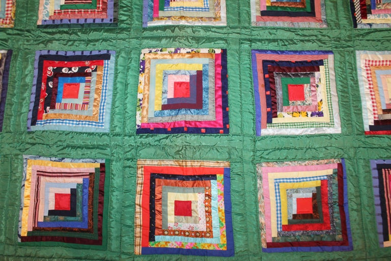 Green satin log cabin quilt in pristine condition. The backing is in a baby blue shambrae cotton fabric.