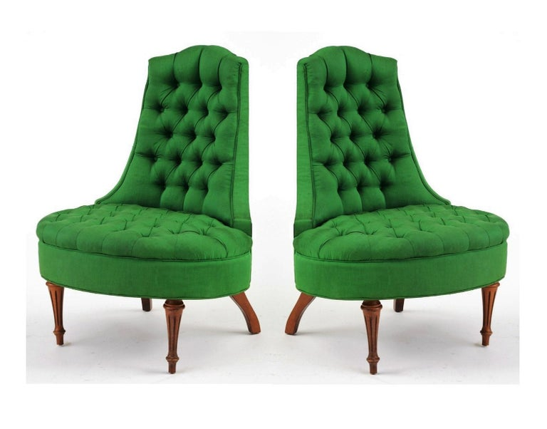 A pair of glamorous Hollywood Regency style tufted lounge chairs. The arm less chairs features a curved back, with an oval seat, standing on reeded front legs. The chair is upholstered in a fresh green silk fabric, with button tufting to back and