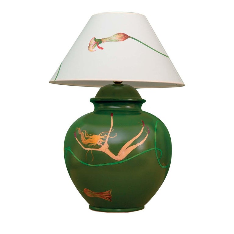 This magnificent piece is the result of masterful, traditional craftsmanship. A versatile and timeless table lamp, it is composed of a base fashioned of green-polished clay, and a white fabric lampshade decorated by hand with a delicate calla