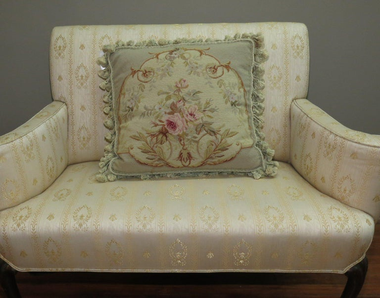 Authentic stand alone pillow made from a 19th century French Aubusson rug with a floral motif with green tasseled corners.   Measures: 19