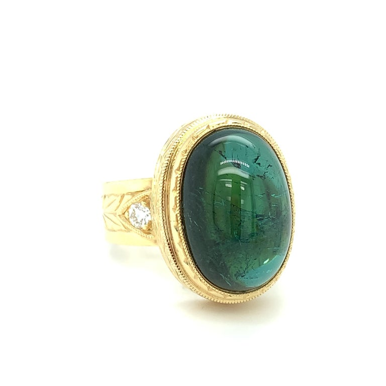 A large, rich 14.01 carat teal green tourmaline cabochon is the focal point of this custom-made signature ring, specially designed for this lovely gem. The tourmaline cabochon is bezel set by hand with a level of precision and skill seldom seen