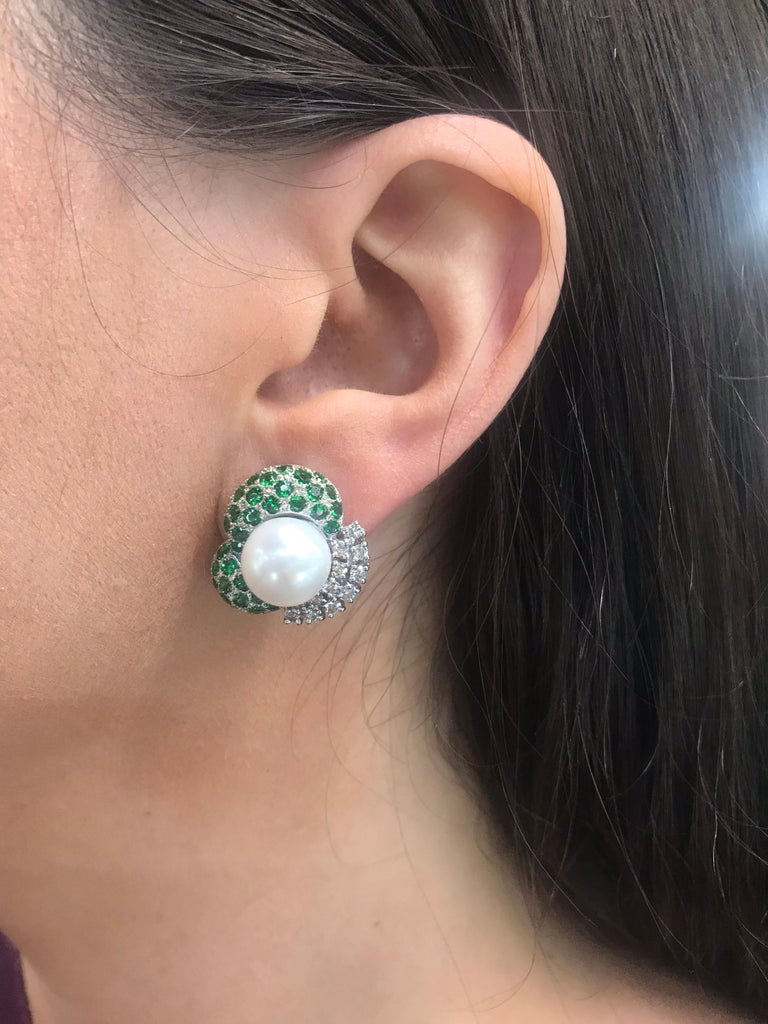 18K White gold stud earrings featuring two white pearls measuring 10-11 MM, flanked with vivid green Tsavorite gemstones weighing 2 carats and round brilliants weighing 0.72 carats. Color G Clarity VS-SI  Very comfortable on the ear!!!