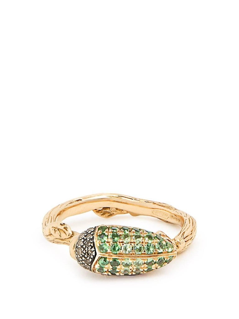 The Tsavorite Scarab Stackable Ring is made of 18k Yellow Gold and Sterling Silver, set with a vibrant green gradient of Tsavorites, and brown diamonds. This ring is from Bibi van der Velden's iconic Scarab Collection and looks elegant when worn