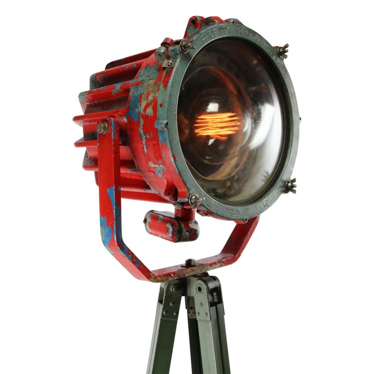 Vintage industrial spotlight on green metal tripod.