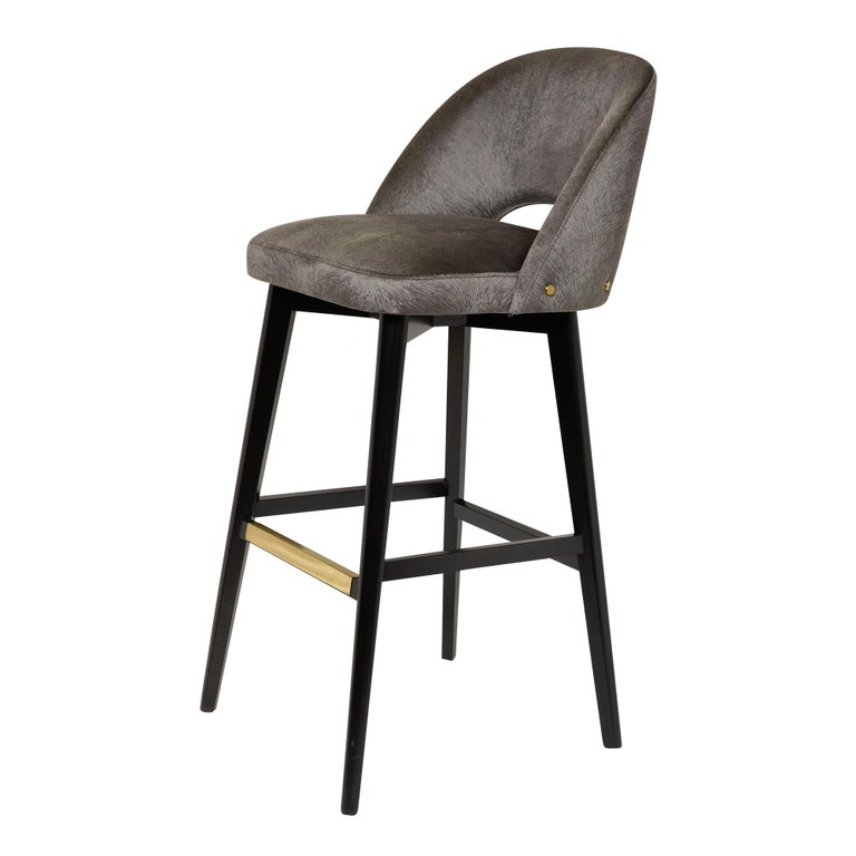 Bar stool with dark wenge stained beech legs, fully upholstered seat and back and brass footrest. Available in counter or bar height and totally customizable including finish, wood, metal and COM. Can be made with a swivel seat.
