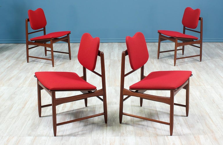 Set of four dining chairs designed by Greta M. Grossman for Glenn of California in the United States circa 1950's. This beautiful set of dining chairs feature a sturdy walnut wood frame with an angled seat and a heart-shaped top back rest. The