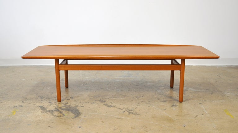 A midcentury Danish modern rectangular cocktail table designed by Grete Jalk, manufactured by Poul Jeppesen, dating from the early 1960s. The table features sculpted raised edges, a distinctive feature of Jalk's designs. A timeless and Classic