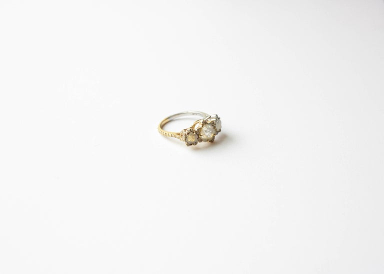 Florette Diamond Ring A platinum and eighteen-karat yellow gold ring set with three unusual florette-cut natural diamonds.  Set in a row are two yellow diamonds and one grey which have been partially enhanced with yellow and white diamonds.