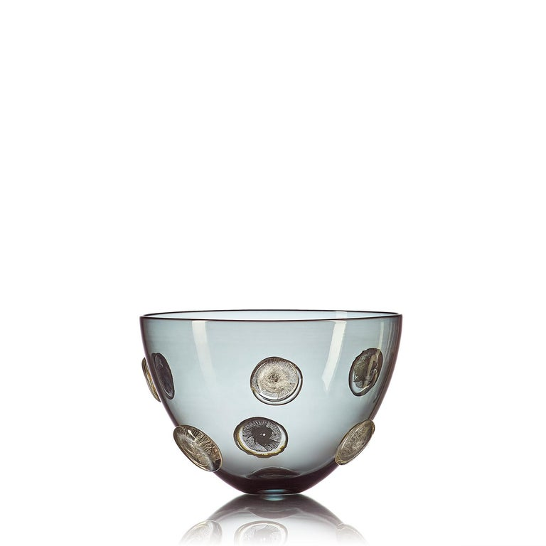 A luminous statement in translucent grey hand blown glass, the Moneto bowl with gold dots features a Cascade of raised metallic coin-shaped dots, encased in clear glass. This large-scale designer vase is hand blown from start to finish by Vetro Vero