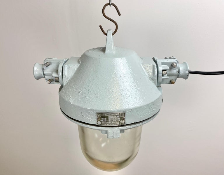 This industrial lamp was made by Elektrosvit in the 1970s. The lam has a grey cast aluminium body and massive protective clear glass bulb. It features a porcelain socket for E27 lightbulbs and new wire. The weight of the lamp is 8 kg.