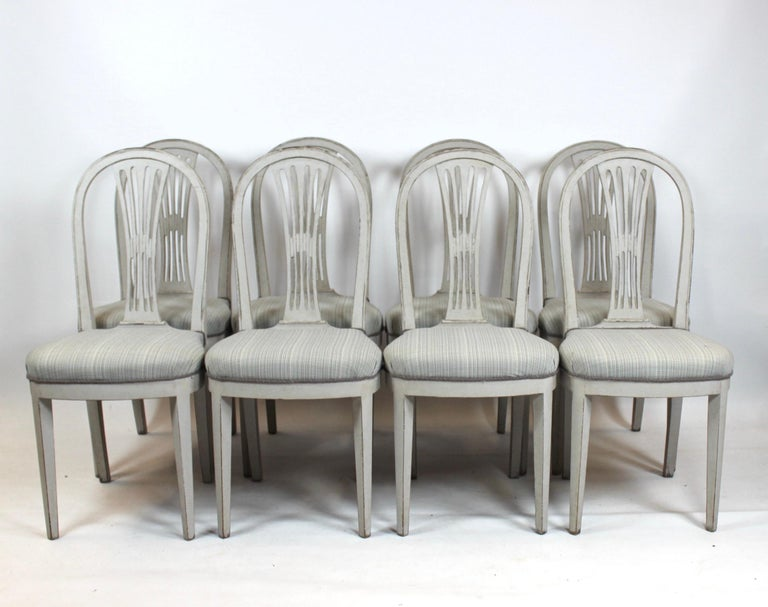 Grey painted Gustavian dining set consisting of large dining table with 4 extension plates and 8 dining chairs. All parts are in great antique condition. Each extension plate is 60cm. The chairs is 99cm in height, 45cm in width, 40cm in depth and
