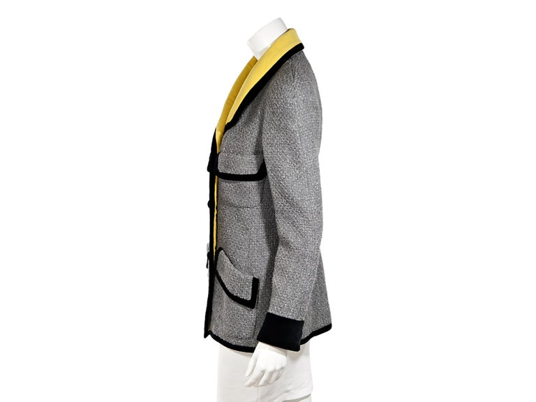 Product details:  Vintage grey tweed jacket by Chanel.  Trimmed with black velvet.  Spread yellow collar.  Long sleeves.  Double-breasted button-front closure.  Four front flap pockets.  34