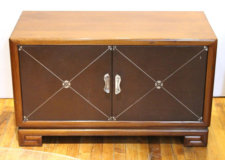 Art Deco low cabinets or nightstands in polished mahogany wood produced in the circa 1940s by Grosfeld House. The pair has silver-embossed leather double doors with Lucite handles and decorative round Lucite handles on the sides, atop Greek key form