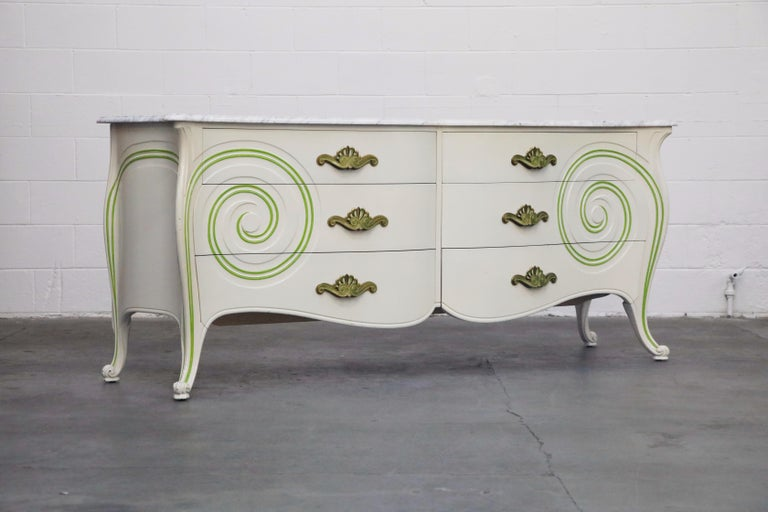 This rare complete bedroom set by Grosfeld House, circa 1940s, includes a figural painted Mahogany dresser cabinet with stunning circulating swirled details, Carrara marble top and intricate brass hardware, a pair of matching nightstands with